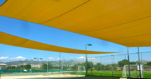 large yellow tensile canopies above tennis courts