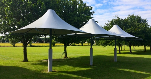 three tensile umbrellas on a green lawn