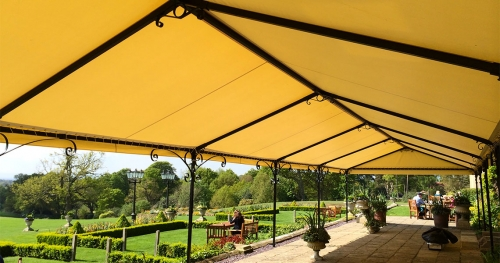 big yellow shade structure in combination with wrought iron