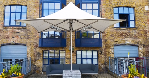 large white unfolding umbrella in front of a building with blue windows
